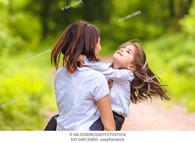 Young mom holds and spins her little girl in forest. Happy mother and daughter moments with love and natural emotion. Photo of young mother and her daughter...