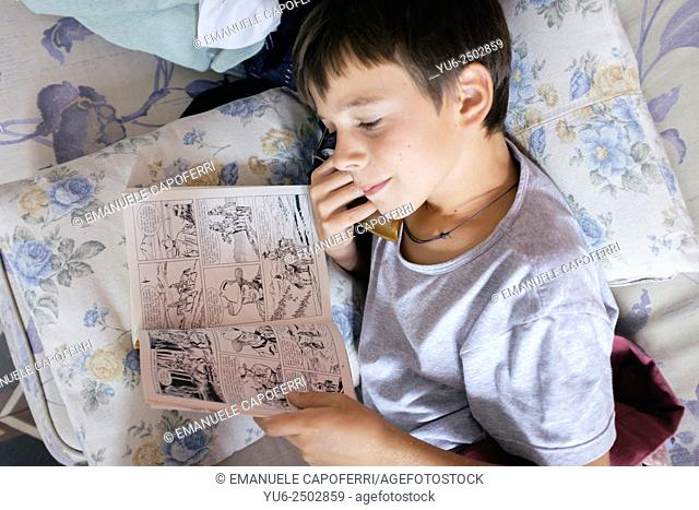 Child reads comic book on the couch at home