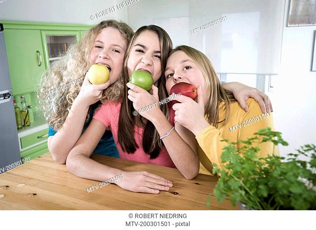 Girls in kitchen eating apples