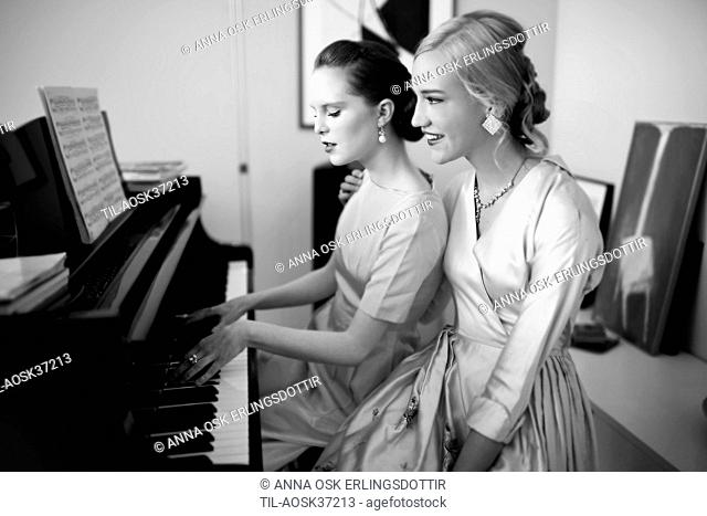 Two sophisticated young women wearing silk dresses sitting by a piano with sheet music