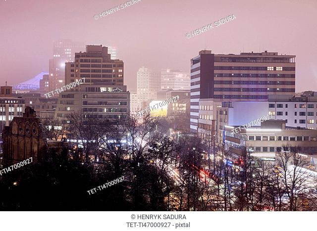Illuminated cityscape in fog