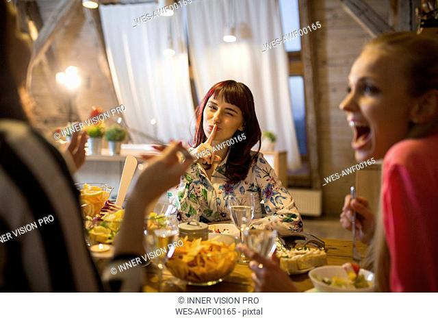 Happy female friends having dinner at home together