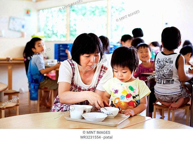 Female teacher sitting at table in a Japanese preschool, helping young boy to eat his lunch