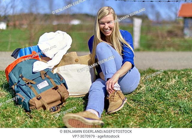 Woman taking rest during hiking adventure at countryside, fixing shoe. Waakirchen, Bavaria, Germany