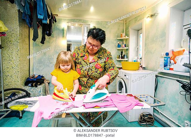 Caucasian grandmother and granddaughter ironing laundry