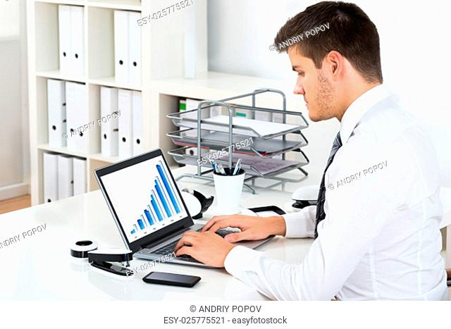 Young Businessman Working With Financial Graph On Laptop At Workplace