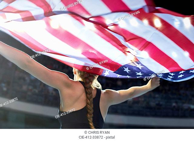 Female athlete running victory lap with American flag