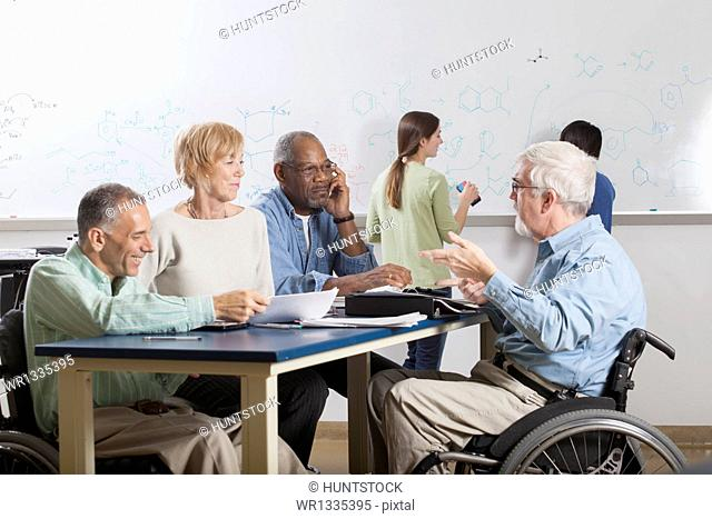 Faculty meeting in an engineering school, one professor with a spinal cord injury and one with Muscular Dystrophy
