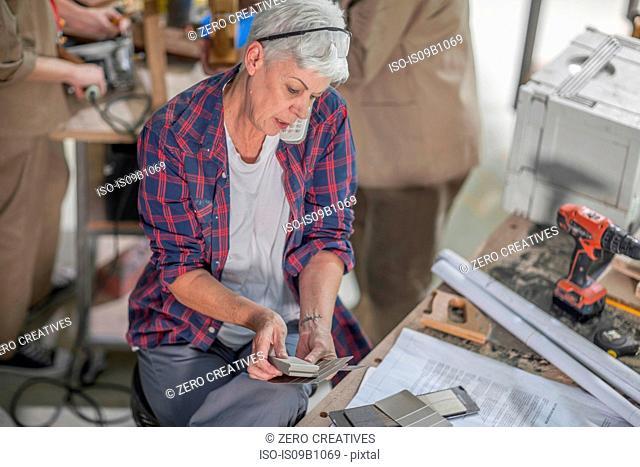 Senior female carpenter looking at swatches in furniture making workshop