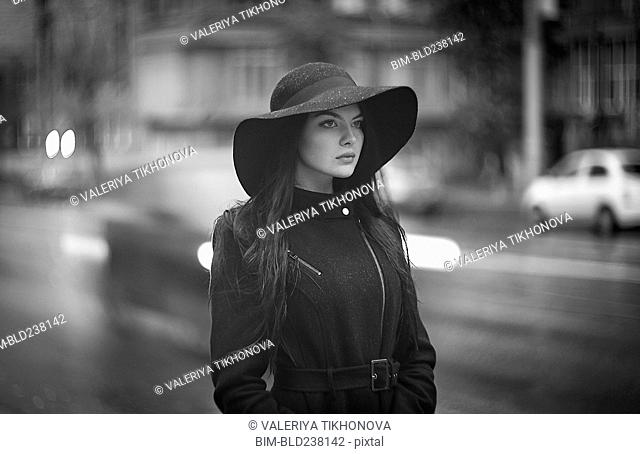 Caucasian woman wearing hat and coat in city