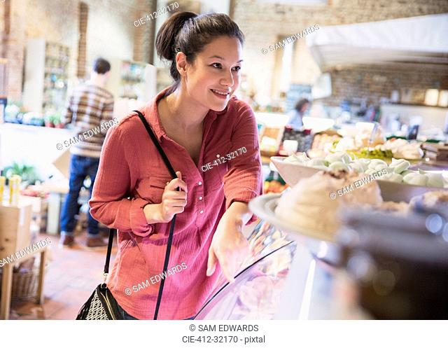 Smiling woman pointing at display case in grocery store