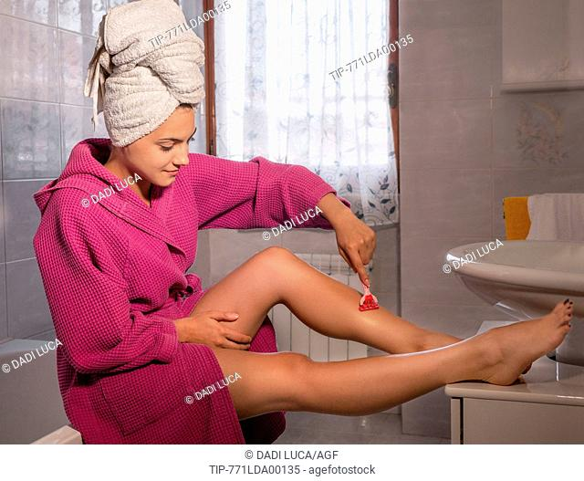 young woman shaving her legs with a razor blade