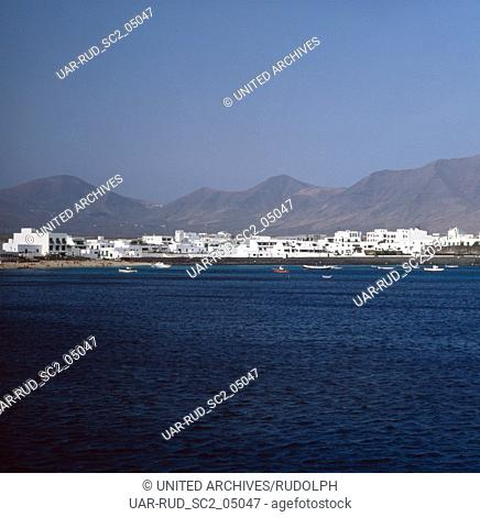 Blick vom Meer auf das Fischerdorf Playa Blanca auf der Kanarischen Insel Lanzarote, Spanien 1980er Jahre. View from the sea to the fishing village of Playa...