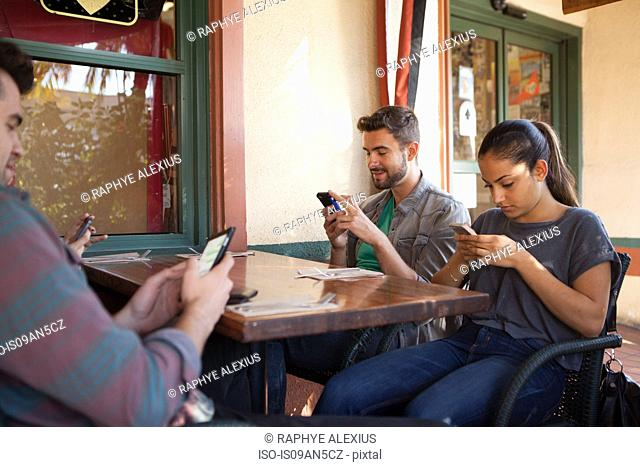 Four friends individually texting on smartphones in vegetarian restaurant