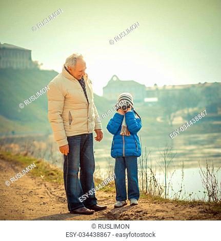 Grandfather and grandson are photographed on a vintage camera. Grandfather and grandchild in a landscape