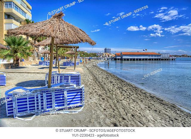 HDR of sunbeds and parasols on Los Alcazares beach and the Mar Menor, Murcia, Costa Calida, South Eastern Spain