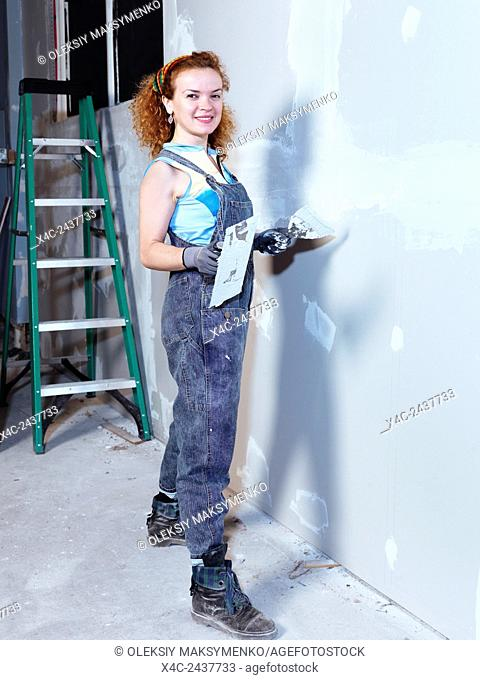 Portrait of a smiling young woman with a trowel and putty knife patching up drywall renovating interior
