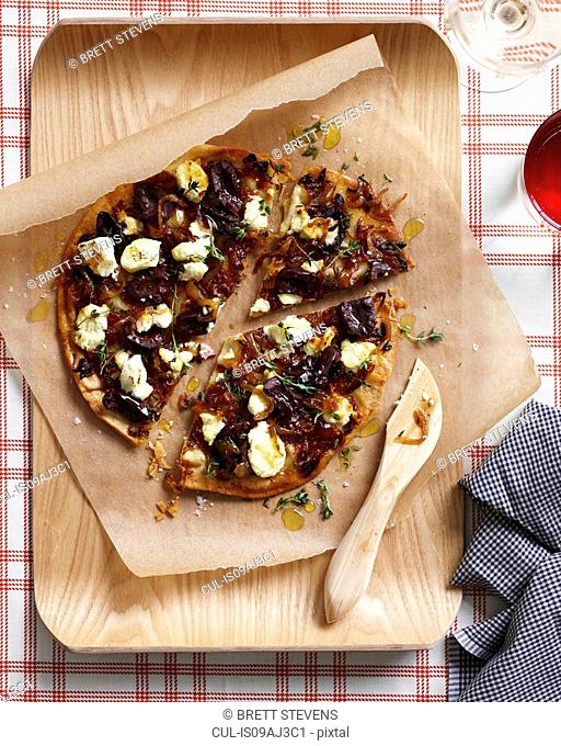 Caramelized onion pizza on chopping board