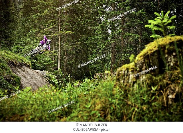 Young male mountain biker jumping over forest gully