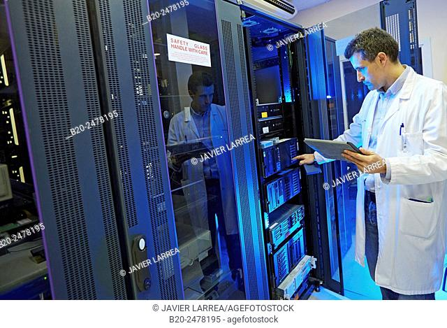 Technician holding digital tablet and standing by cabinet at data processing center, Hospital Donostia, San Sebastian, Basque Country, Spain