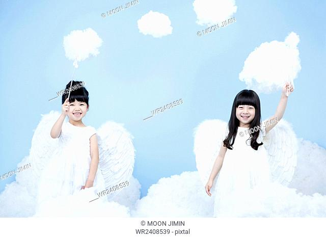 Two girls in angel costume holding magic stick each and smiling in the background representing heaven