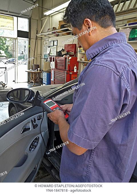 A technitian performes an emission control check on an automobile in California