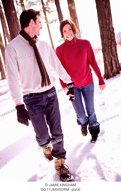 Couple walking through snowy woods