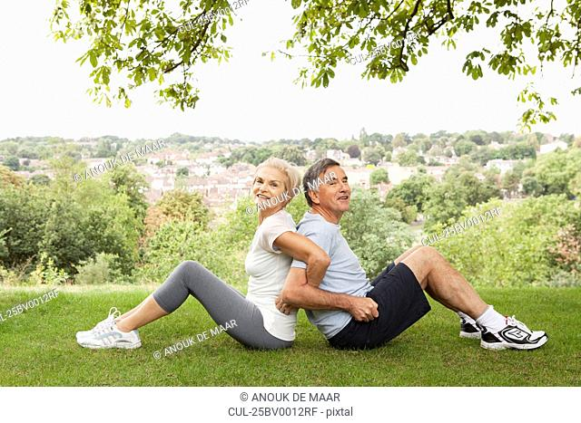 Mature couple stretching back to back