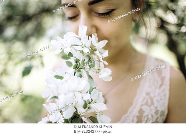 Middle Eastern woman smelling flowers
