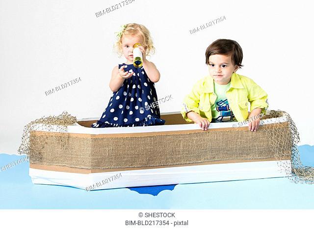 Children playing in cardboard boat