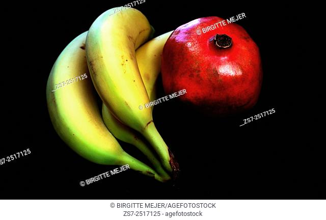 Studio shot of 3 Bananas and a pomegranate