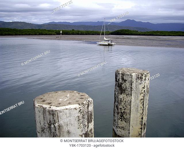 Stranded catamaran during low tide in stormy weather inthe background and two berth poles in the foreground at Port Douglas, Queensland, Australia