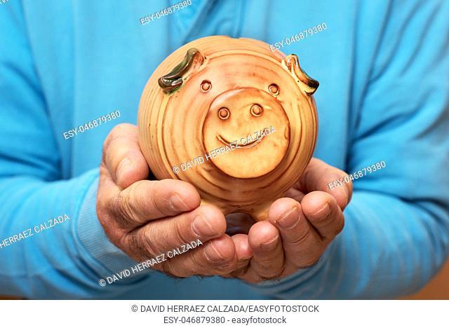 Senior holding piggy bank in hands