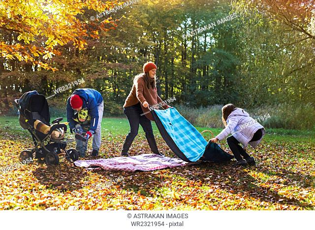 Family preparing for picnic in forest