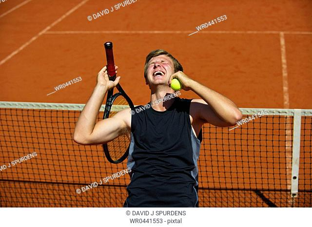 A tennis player celebrates winning the game