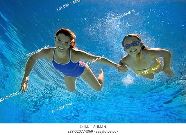 Mother and daughter (8-10) in swimming pool, smiling, portrait, underwater view