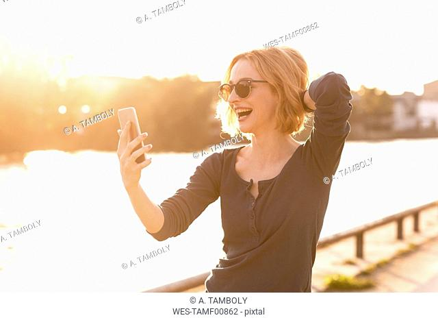Happy young woman taking selfie with smartphone at backlight