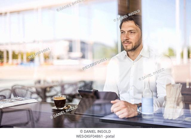 Businessman behind windowpane using tablet in a cafe