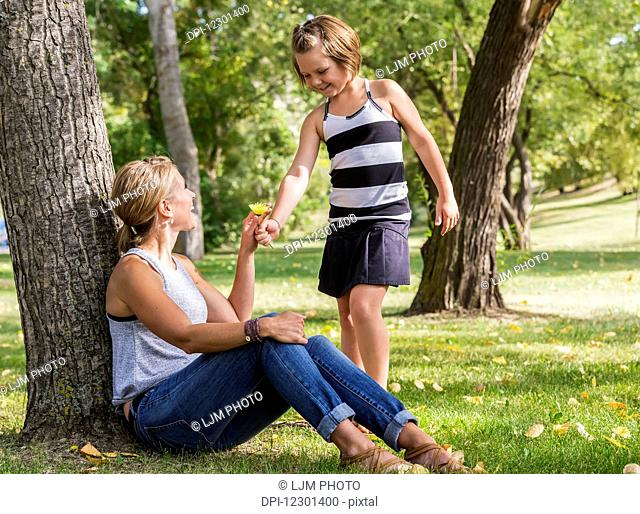 Mother getting a flower from her daughter while spending quality time at a park during a family outing; Edmonton, Alberta, Canada
