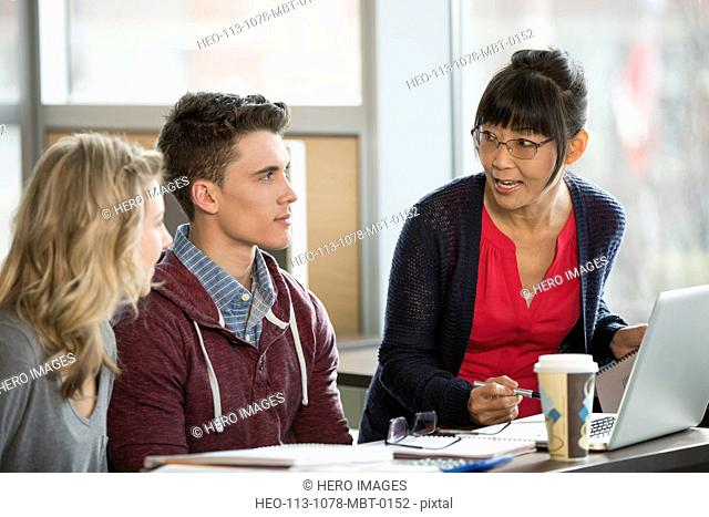 Professor and college students talking at table