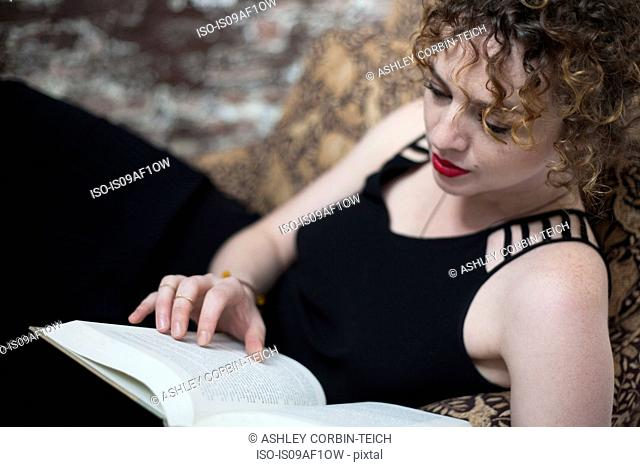 Portrait of young woman reclining and reading book