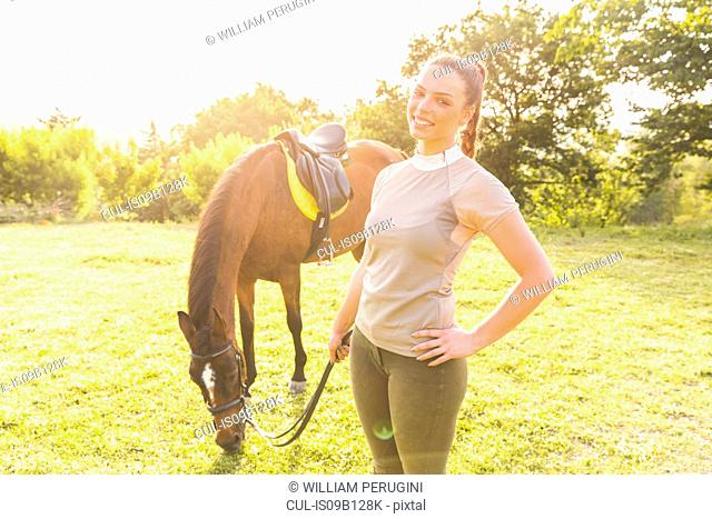 Woman holding tethered horse looking at camera smiling