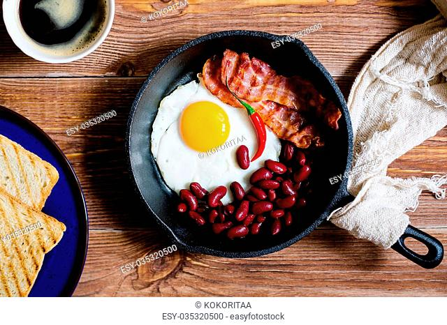 english breakfast in rustic style. fried eggs with beans and bacon on a frying pan. toasts on a blue plates. close up, top view