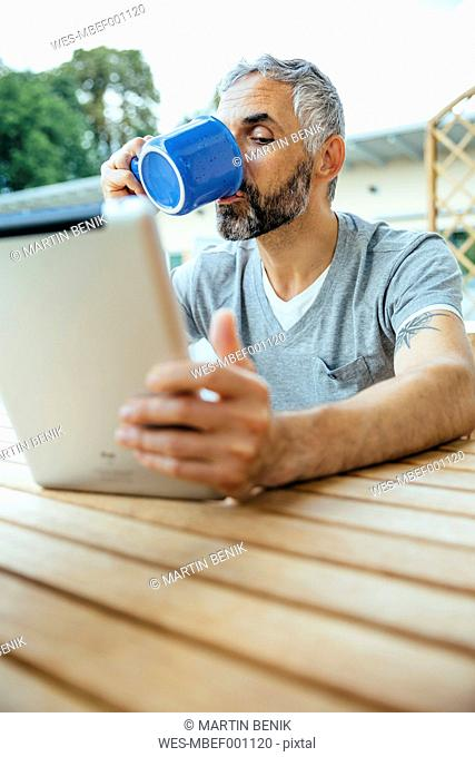 Portrait of man sitting on his balcony drinking coffee using digital tablet