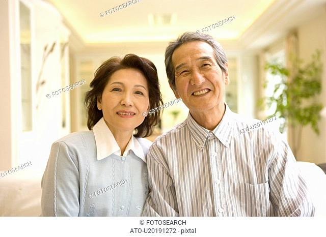 A Senior Adult Couple Smiling at Camera in a Room, Front View, Differential Focus