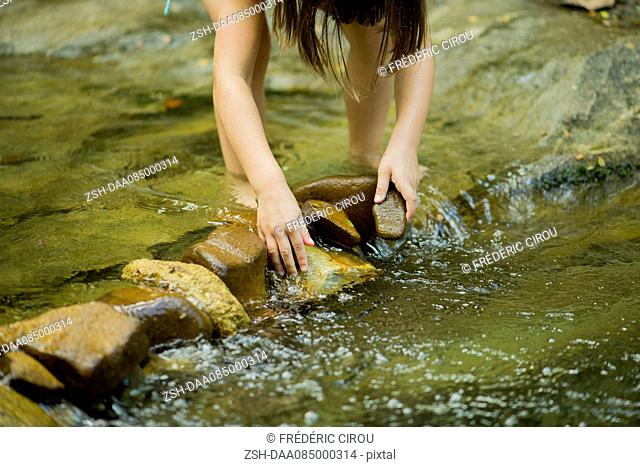 Child using rocks to build a dam in a shallow stream