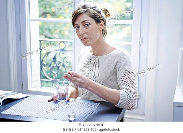 woman pouring essential oil in a glass of water