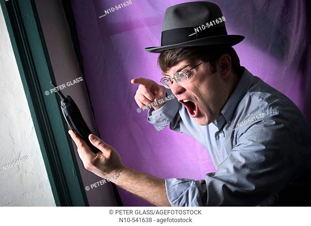 Young man, wearing glasses and a hat, yelling at his portable phone