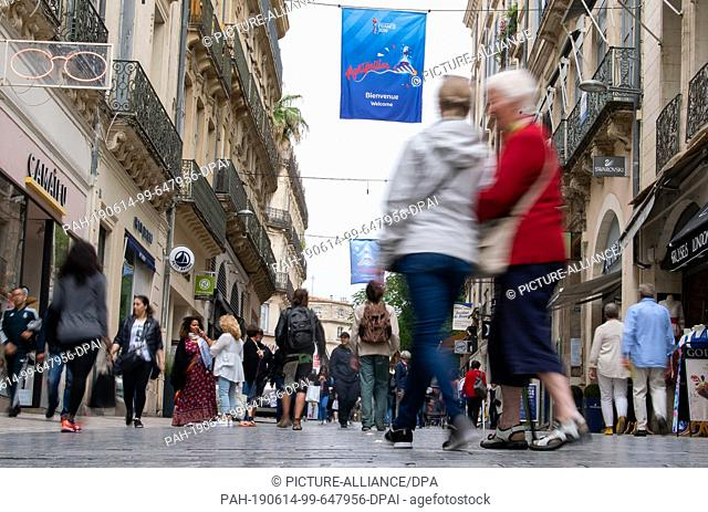 """14 June 2019, France (France), Montpellier: Football, women: WM, Montpellier : Passers-by walk under flags of the world championship on which """"""""Montpellier"""""""" is..."""