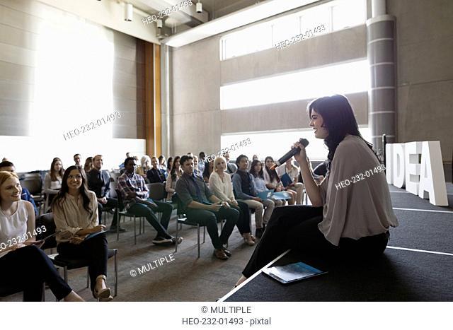 Speaker sitting addressing audience stage near Idea text